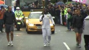 Linvoy Primus with the Olympic flame