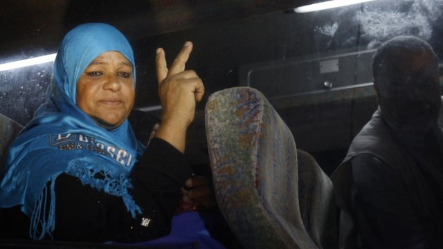 Relative of a Palestinian prisoner on her way to visit her relative jailed in Israel gestures from inside a bus before it leaves Gaza City 16 July 2012