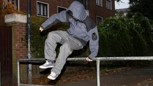 A teenage boy jumping over a barrier