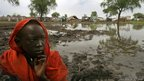 A Sudanese refugee sits by the flooded area where hundreds of refugees live in Jamam refugee camp, South Sudan.