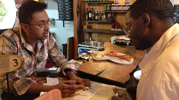 Mambo Pizza&#039;s Nish Shah explains to a customer how to check in using the NikoHapa service using his mobile phone