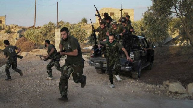 Fighters of the Free Syrian Army run for cover