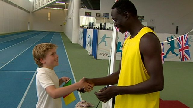 Athlete shakes hand with school boy