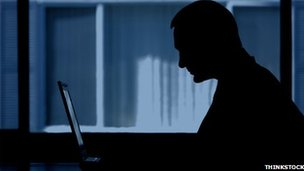 A man sits in the dark on a computer