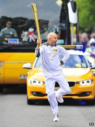 Torchbearer Colin Bentley takes the Olympic torch through Brighton on day 60