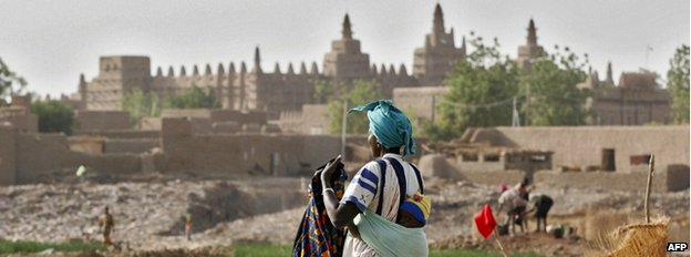 This photo taken on 8 February 2005, shows a woman and her child resting, with the Great Mosque of Djenne in the background in Mali