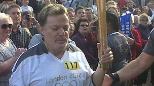 Eddie Izzard surrounded by crowds with the torch