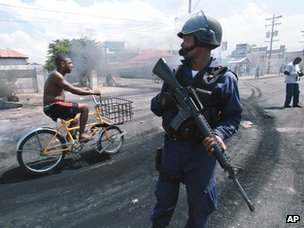 A man rides by the remains of a burning barricade while a riot police officer stands guard on Hagley Park Road in Kingston Jamaica on Tuesday April 20, 1999.