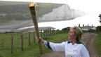 Kathy Gore runs with the Olympic flame at Seaford Head