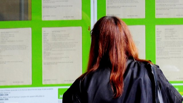 Young woman looking into Jobcentre window