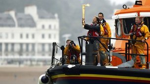 The torch is held aloft by security officer Suzia on board an RNLI lifeboat