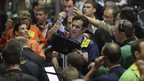 Traders react in the Corn Options Pit at the CME group in Chicago, 11 July 2012