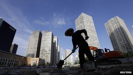 "A labourer works at a construction site in Beijing""s central business district 12 July, 2012"