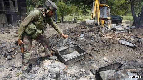 An Indian soldier searches for the bodies of suspected militants in the rubble of a house after a gun battle in Baban, 90km (55 miles) north of Srinagar