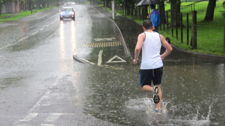 runner going through huge puddle