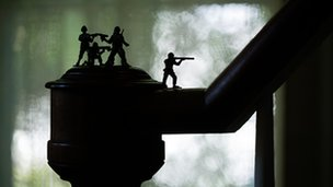 Silhouette of toy soldiers on top of a banister in front of a window with net curtains.