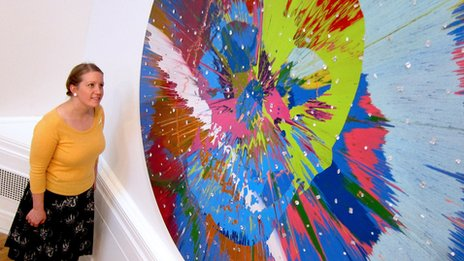 Curator Louisa Briggs with Damien Hirst painting