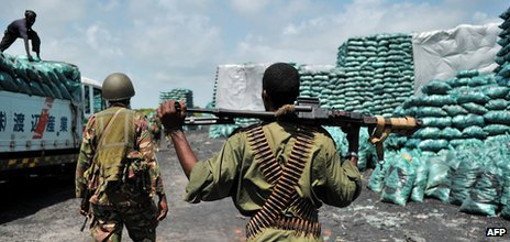Militia allied with the government of Somalia and Kenyan soldiers walk through a charcoal loading area in Burgabo, southern Somalia on 14 December 2011