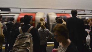 Commuters wait to board a Tube train at Holborn Underground Station