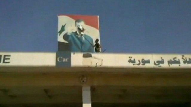 Video was posted on the internet of rebels defacing a poster of President Assad at the Bab al-Hawa crossing