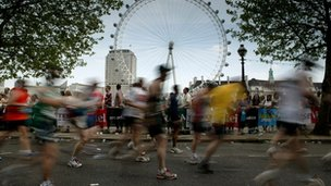 Runners go past the London Eye during the Flora London Marathon 2007