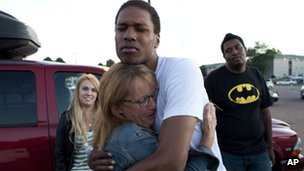 A woman hugs a young man after the shooting