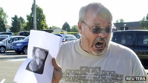 Tom Sullivan holds up a photo of his son Alex Sullivan pleading the media to help find him, outside Gateway High School a few blocks from the scene of the Century 16 Theatre shootings in Aurora, Colorado 20 July 2012