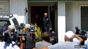 A police officer walks from the front door of the home of Arlene Holmes in Rancho Penasquitos, California 20 July 2012