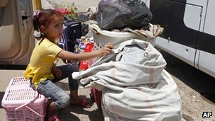 Layla Fadhil, an Iraqi refugee, sits with her family&#039;s belongings after her arrival from Syria to the Mansour neighbourhood of Baghdad, Iraq