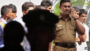 A Sri Lankan officer speaks on a mobile phone in front of the court house in Colombo, Sri Lanka, Friday, July 20, 2012.