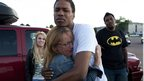 A mother hugs her daughter's friend, Isaiah Bow, 20, while eyewitnesses Emma Goos, 19, left, and Terrell Wallin, 20, right, look on - 20 July 2012