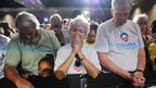 Supporters of President Barack Obama bow their heads at a rally