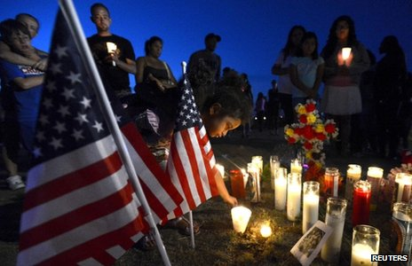 A girl places a candle by an American flag during a vigil for those shot at a cinema in Aurora, Colorado (20 July 2012)