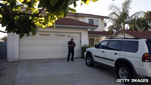 A policeman stands guard outside the home of James Holmes' parents in San Diego (20 July 2012)