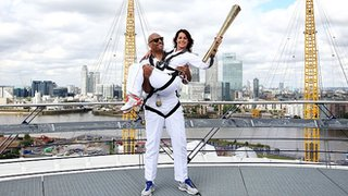 Nadia Comaneci, right, and John Amaechi with the Olympic Torch