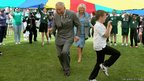 "Prince Charles and the Duchess of Cornwall take part in a Youth Showcase ""Parachute game""."