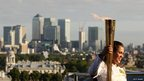 Natasha Sinha, 15, holds the torch aloft, against a backdrop of the skyscrapers of Canary Wharf