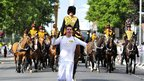 Paratrooper Jaco van Gass carries the torch in front of mounted guardsmen from the King&#039;s Troop Royal Horse Artillery