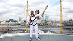 John Amaechi carries Nadia Comaneci, with the torch, at the top of North Greenwich Arena