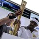 Phillips Idowu places the torch in a holder at an event in Stratford