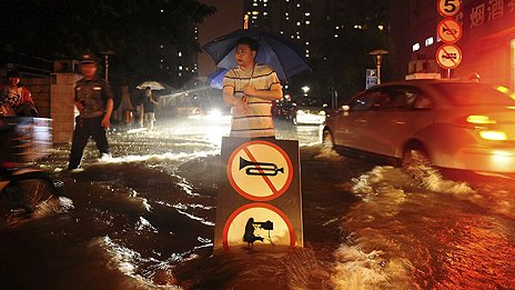 A Chinese man uses a signboard to signal motorists driving through flooded street following a heavy rain in Beijing Saturday, July 21, 2012