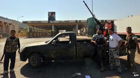 Syrian rebels stand near the Bab al-Hawa border post with Turkey (20 July 2012)