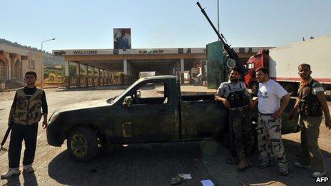 Syrian rebels stand near the Bab al-Hawa border post with Turkey (20 July 2012)