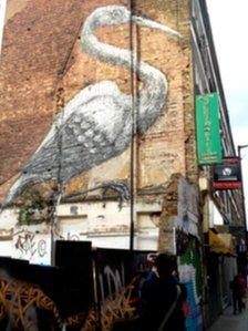 Tourist taking a photograph of Roa&#039;s crane just off Brick Lane