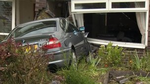 Car embedded in house