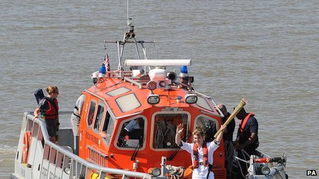 Aaron Reynolds carries the flame across the Thames in a London Fire Brigade boat