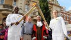 Luke Williams passed the Olympic flame to Elise Cobain outside Redbridge Town Hall in front of Redbridge Mayor Muhammed Javed (second right).