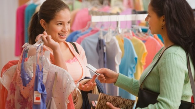 Mother giving daughter a card to pay for clothes with