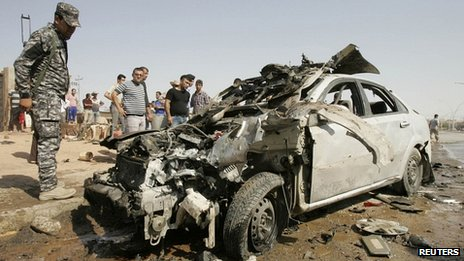 Iraqi policeman looks at car wrecked by bombing in Kirkuk (23/07/12)
