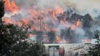 A wildfire approaches trucks in La Jonquera on July 22